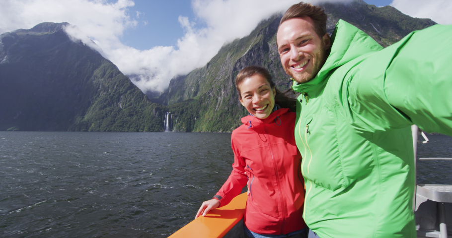 Couple having fun taking selfie video using smart phone on cruise ship, Milford Sound, Fiordland National Park, New Zealand. Multicultural couple smilng having fun laughing on travel vacation.