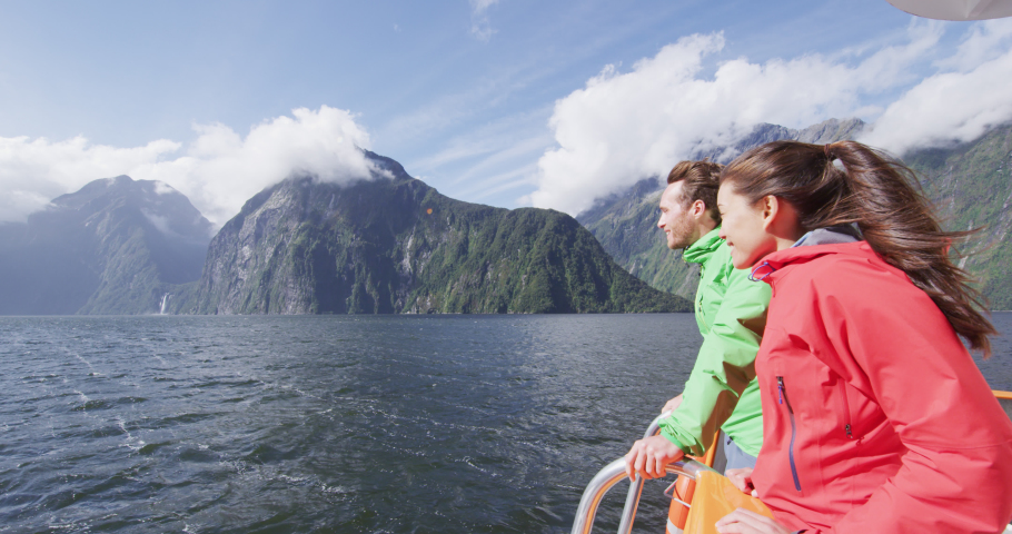 Cruise ship tourists on boat tour in Milford Sound, Fiordland National Park, New Zealand. Happy couple on sightseeing travel on New Zealand South Island. SLOW MOTION Cinema Camera.
