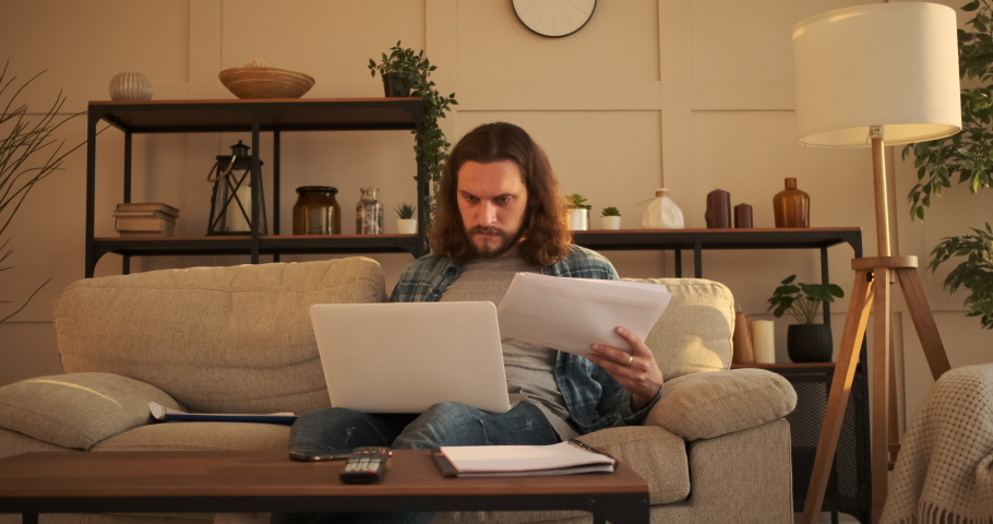 Man analyzing document and using laptop at home | Shutterstock HD Video #1056373787
