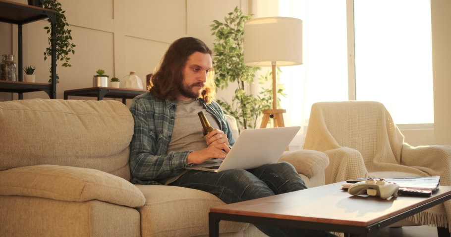 Man using laptop and drinking beer at home | Shutterstock HD Video #1056373904