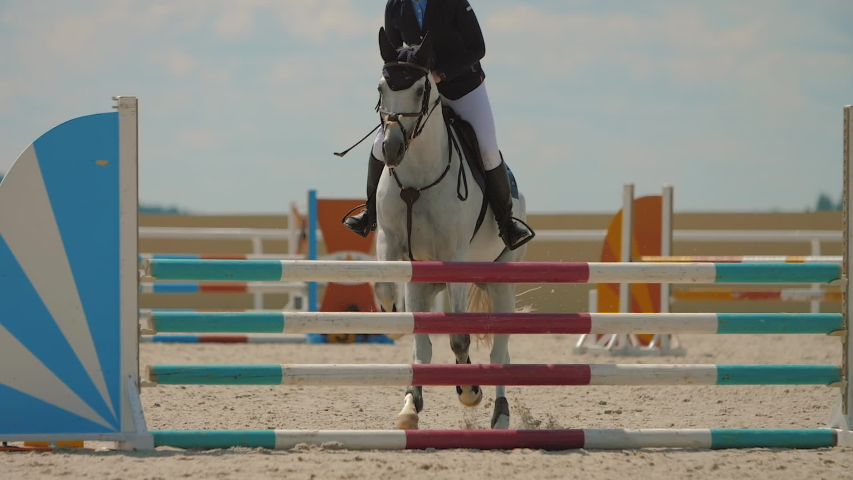 Competitive woman rider on horse jumping over obstacles, slow motion. White horse leaping fence on sandy parkour riding arena, equestrian competition outdoors. Training jumping hurdle.