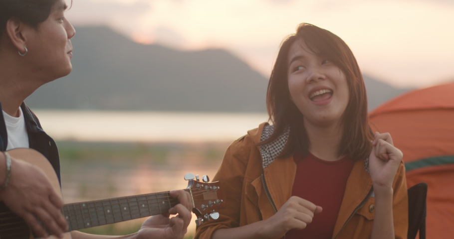 Young asia campers couple playing guitar serenading each other near beach. Male and female travel happy romantic moment when sunset in evening. Outdoor activity, adventure travel, or holiday vacation. Royalty-Free Stock Footage #1056376790