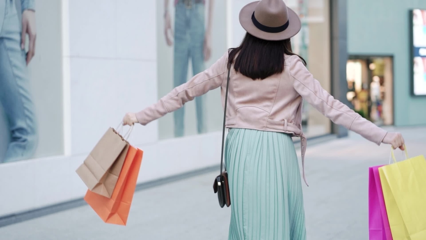 Young attractive woman walks with colorful shopping bags around shopping mall after quarantine. Back view. | Shutterstock HD Video #1056377369