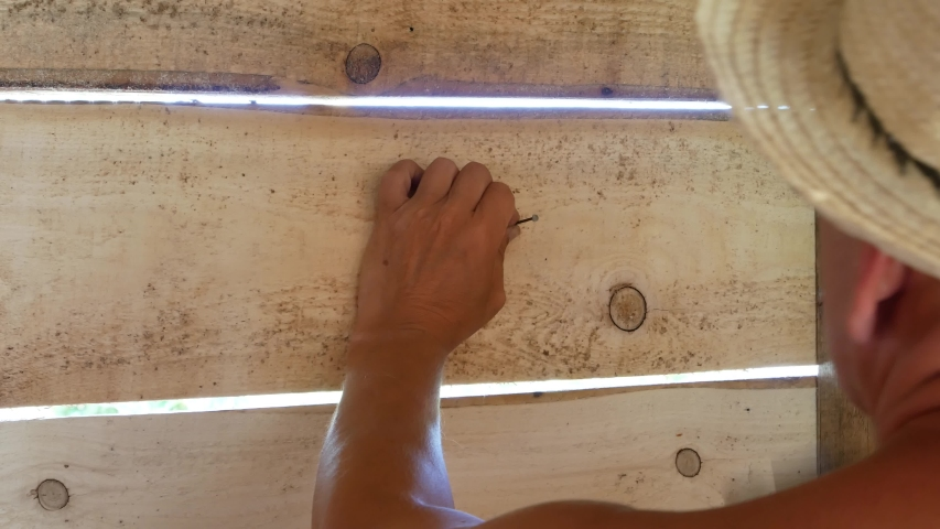 One elder man hammers a nail into a wooden shed wall and hangs his hat on it | Shutterstock HD Video #1056380843