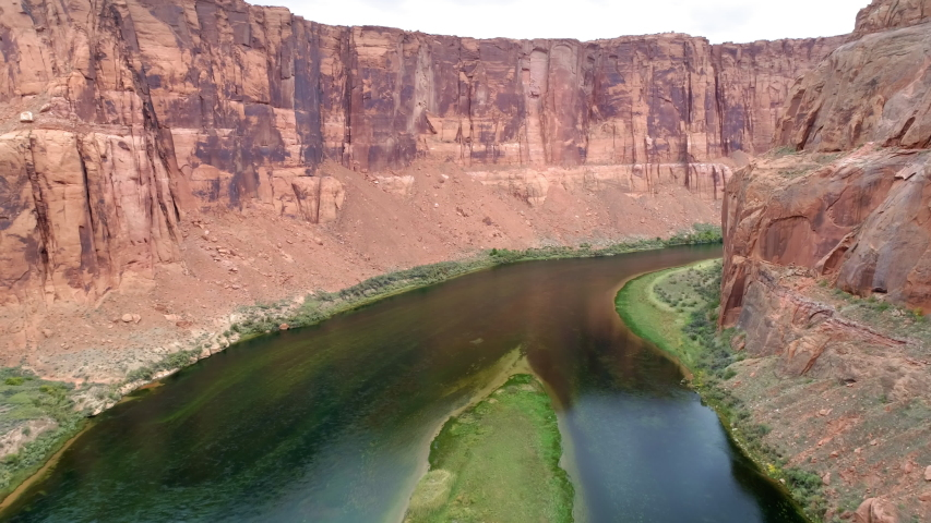 4K aerial slow motion flight in the deep beautiful red canyon with sheer red sandstone cliff walls. Camera moving forward above dramatic surface at beginning of Grand Canyon with green Colorado river