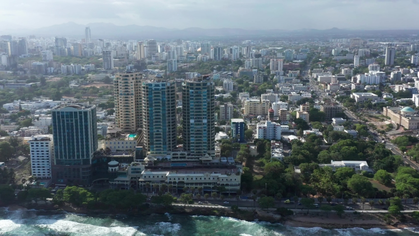 Incredible esenico flight from the malecon of Santo Domingo where we see the big city and the Caribbean sea, lots of waves and pleasant weather.   Shutterstock HD Video #1056386801