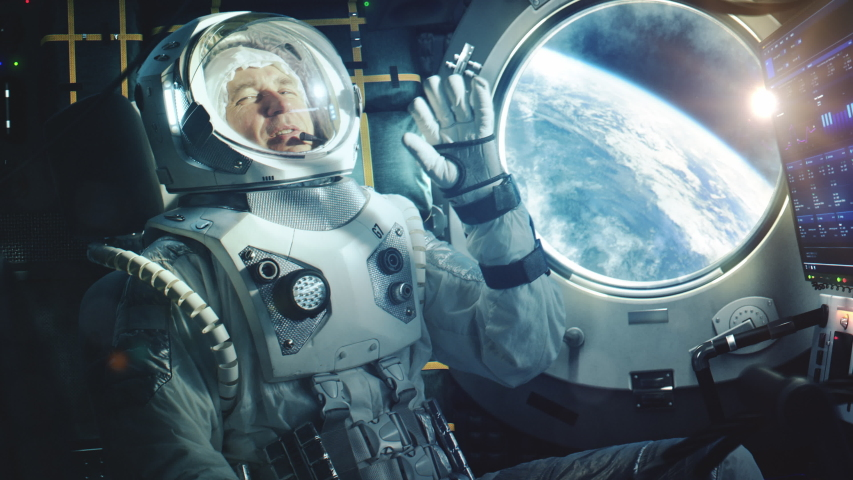 Portrait of a Happy Astronaut on a Space Ship In Orbit. Cosmonaut in a Futuristic Suit is Full of Joy and is Waving Hand on a Video Call. VFX Graphics Footage from the International Space Station. | Shutterstock HD Video #1056387902