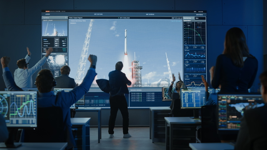 Group of People in Mission Control Center Witness Successful Space Rocket Launch. Flight Director is Pacing Nervously in Front of the Screen and Punches the Air in Celebration. Team Claps Hands.