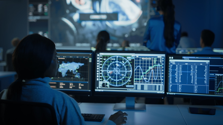Group of People in Mission Control Center Establish Successful Video Connection on a Big Screen with an Astronaut on Board of a Space Station. Flight Control Scientists Sit in Front of Computers. Royalty-Free Stock Footage #1056387947