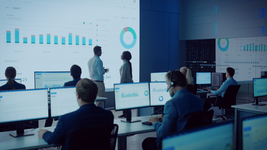 Two Financial Data Analysts Having a Meeting in a Modern Monitoring Office with Analytics Feed on a Big Digital Screen. Monitoring Room with Brokers and Finance Specialists Sit in Front of Computers.