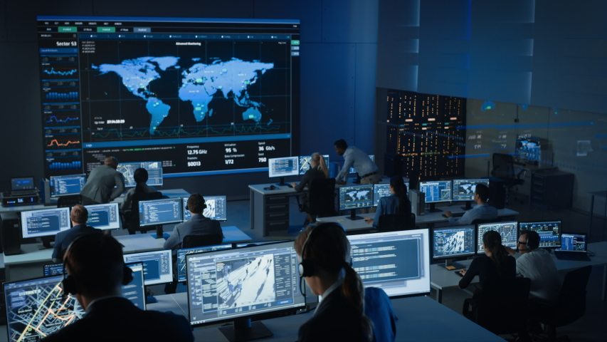 Government Officers Work on a Computers with Surveillance CCTV Video in a Police Monitoring Center with Global Map Tracking on a Big Digital Screen. Employees Sit in Front of Displays with Big Data Royalty-Free Stock Footage #1056388013