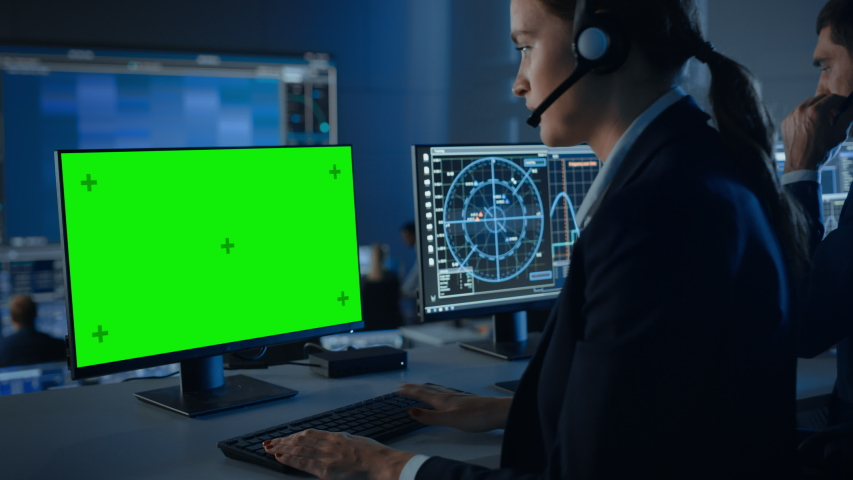 Green Screen Horizontal Mock Up on a Computer Display Used by a Female Controller in a Mission Control Center Room with Other Scientists. Team of Engineers Work in Monitoring Room Full of Displays.