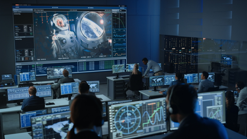 Group of People in Mission Control Center Establish Successful Video Connection on a Big Screen with an Astronaut on Board of a Space Station. Flight Control Scientists Sit in Front of Computers. Royalty-Free Stock Footage #1056388142