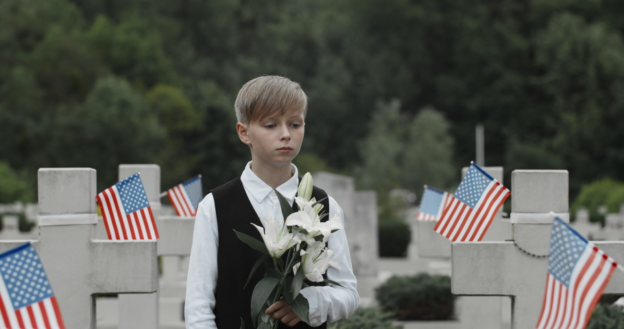 Close up of teen boy holding lily flowers while standing near grave of his father. Kid honoring his dad soldier at cemetery. Concept of memorial day. American flags at stone crosses.