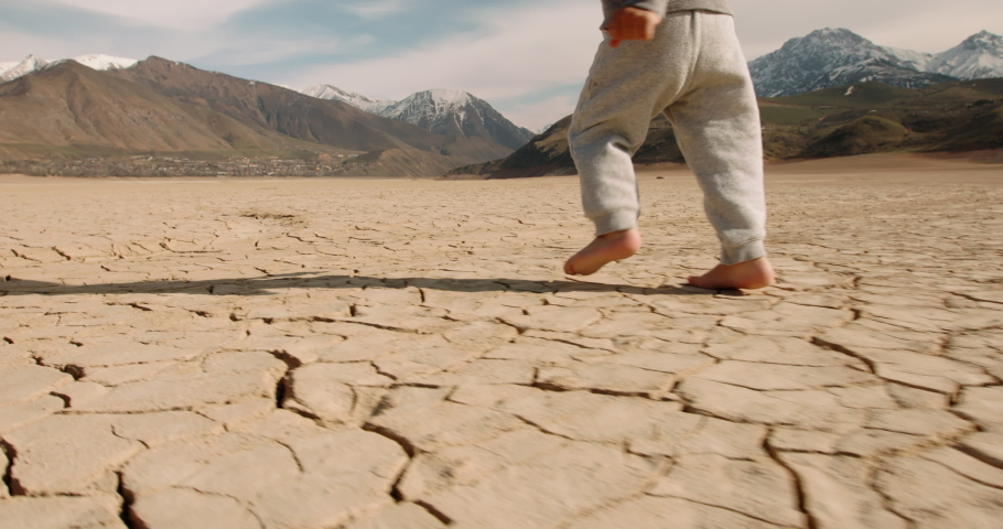 Close up shot of legs of baby boy running on cracked ground, destroyed by erosion, desertification and global warming - environmental issues, save our planet 4k footage Royalty-Free Stock Footage #1056392747