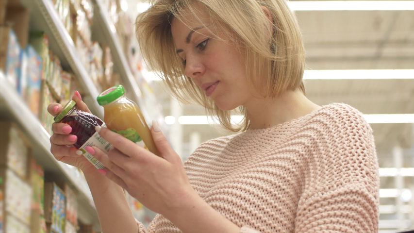 One 30s Carefree Women Read Apple Vitamin on Label by Fruit Juice Stand Shelf Indoor Store. Alone Handsome Girl Search Bio Nature Drinking Vegetable. Real Analyze Select in Water Department Closeup 4k