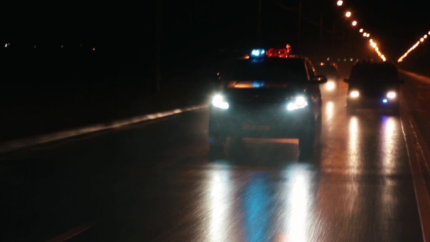 Police cars are chasing an intruder's car in the hard rain. Outdoor front view of police traffic auto driving.  Royalty-Free Stock Footage #1056395120