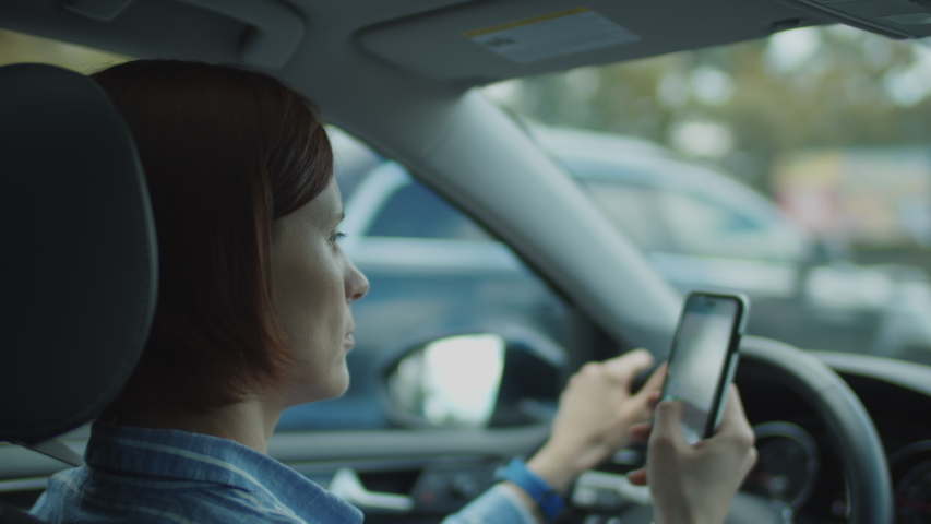 30s woman driving and holding mobile phone in hands. Female driver holding steering wheel and using cell for online map. City cars driving in windshield.