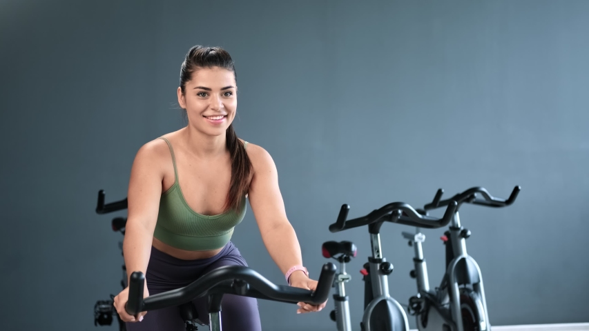 Joyful fitness lady cyclist enjoy cardio workout at modern cycling studio. Face of beautiful athletic girl with perfect skin during training stationary bike zoom in. Shot on RED Raven 4k Cinema Camera