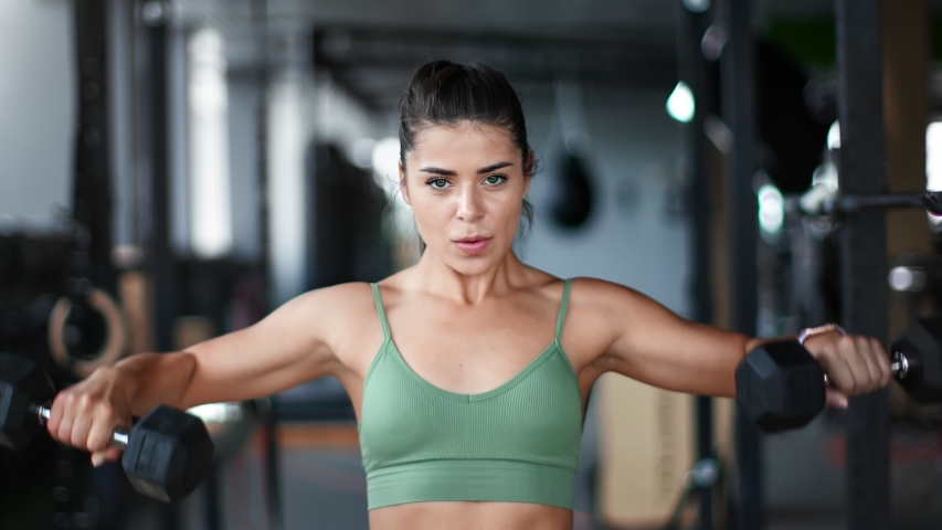 Mixed race bodybuilder female lifting dumbbells and breathing training shoulders. Portrait of beautiful woman professional athlete during muscle workout at gym. Medium shot on RED camera