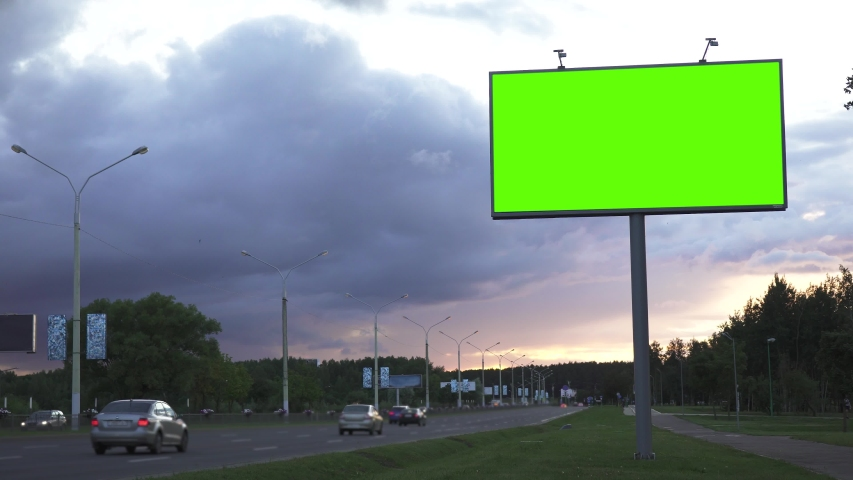 Mock up concept. Green screen billboard on the the highway against the background of the evening sky.