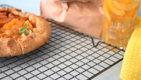 Woman hand put a galette tart pie with fresh ripe apricot on the plate.