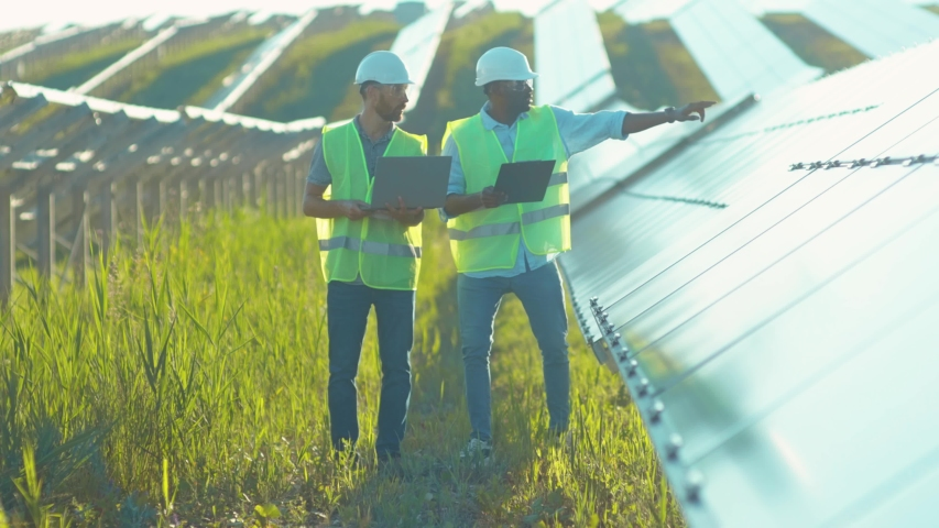 Close up engineers use laptop and project plan on the solar farm in special uniform standing look around discuss the installation of sunny batteries electricity environmental slow motion