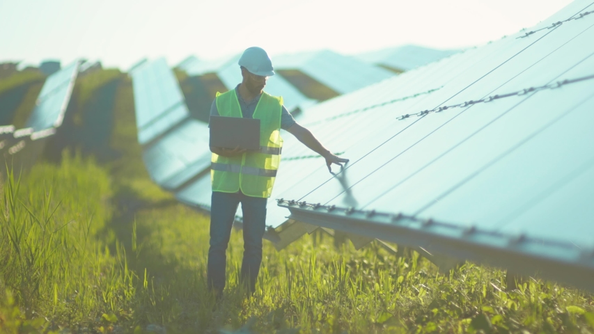 Engineer working use laptop stand near solar batteries construction renewable power worker man technology modern electricity energy slow motion Royalty-Free Stock Footage #1056411974