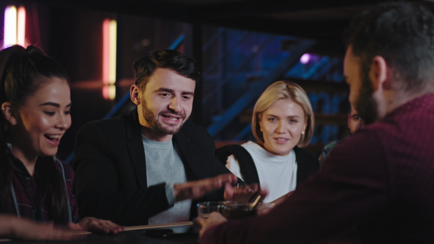 Happy and excited friends in a bar shaking hands they waiting for the drinks get the drinks and start to enjoy the night together smiling they feeling so excited | Shutterstock HD Video #1056412292