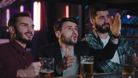 Three guys charismatic closeup to the camera football fans in a pub while drinking beer watching the match they are so emotional in a sport bar