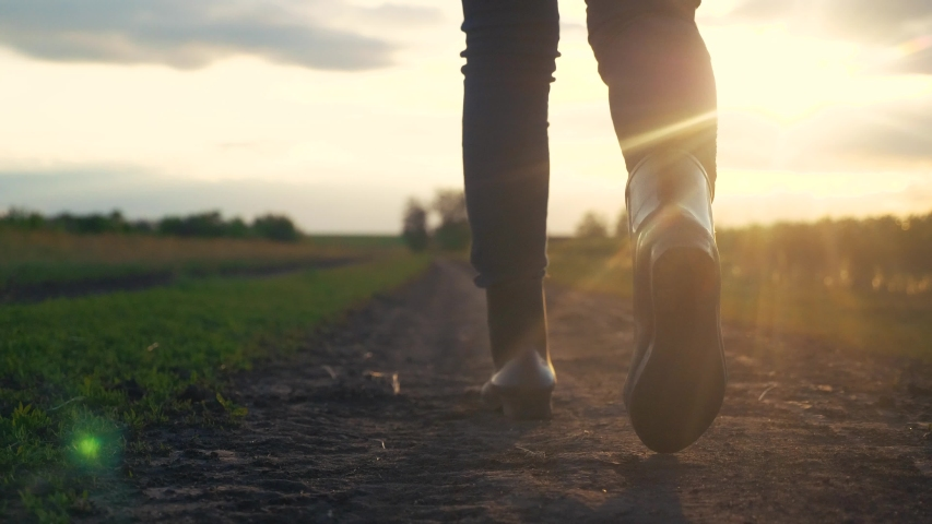 Agriculture. girl farmer in rubber boots walks along a country road near a green field of wheat grass. farmer worker goes home after harvesting end of the working day feet in rubber boots agriculture | Shutterstock HD Video #1056415271