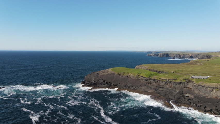 Aerial view over the Castle point, Kilkee, County Clare, Ireland. This exposed cliff edge and popular fishing spot is the original location of Dunlicky Castle. Wild atlantic way. Royalty-Free Stock Footage #1056418145