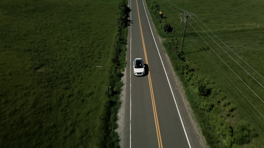 A White Car Driving On The Asphalt Road In Quebec, Canada On A Bright Weather - ascending drone shot (backward)