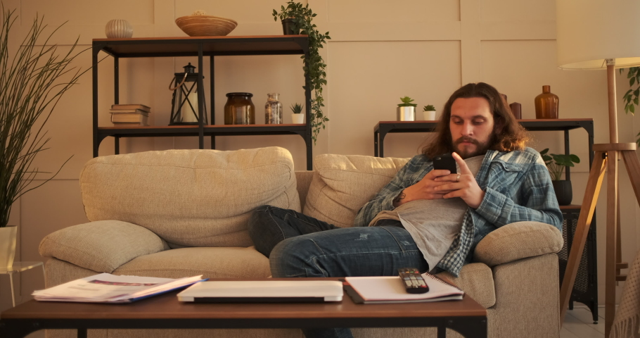 Man text messaging on mobile phone at home | Shutterstock HD Video #1056425537