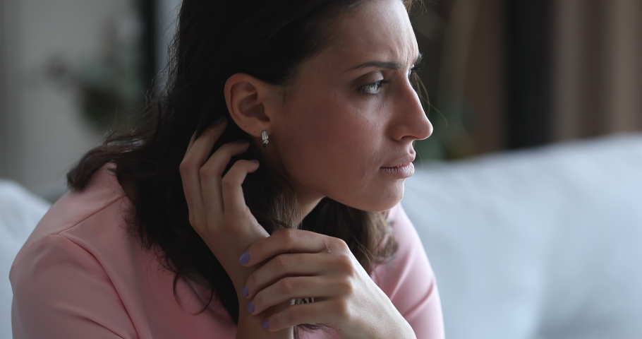 Close up middle eastern ethnicity pensive woman sit on couch alone waits feels jealousy. Break up, marriage split, divorce, bullying and discrimination, unexpected pregnancy abortion decision concept