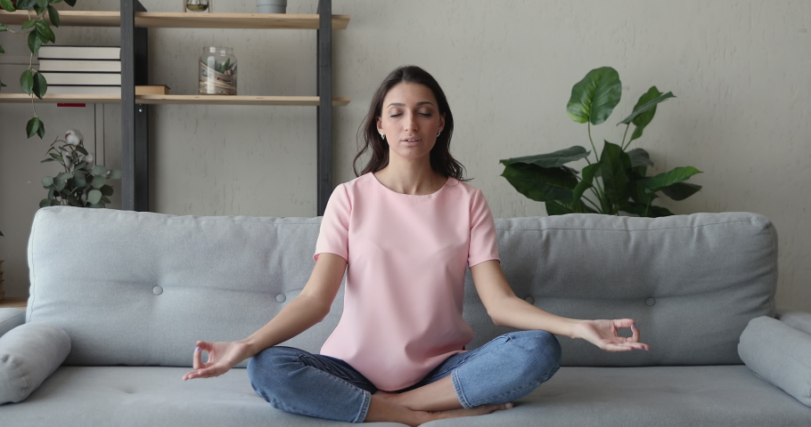 Mixed race Indian woman sit cross-legged on comfy sofa in living room closed eyes do meditation practice feels inner harmony and balance, improve self-conscious, mindfulness state, no stress concept | Shutterstock HD Video #1056430088