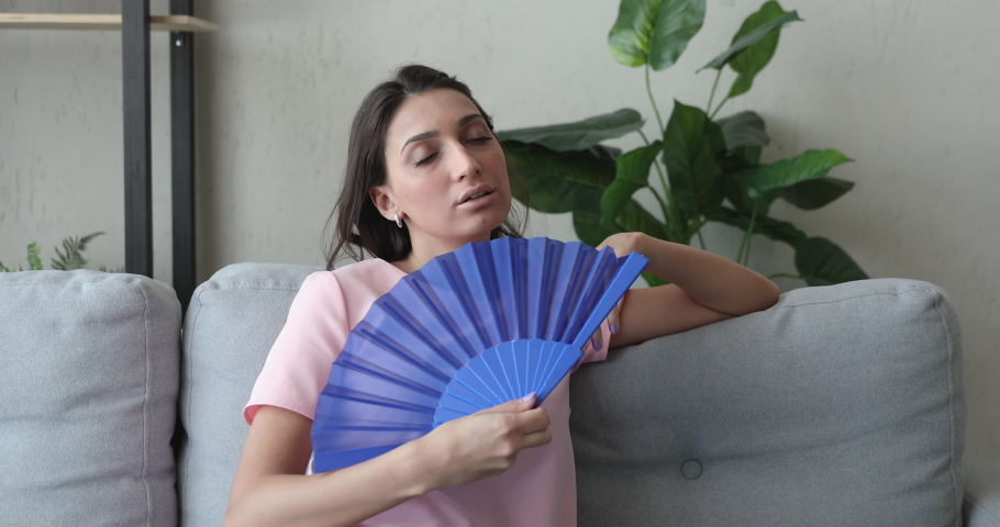 Sweaty young middle eastern ethnicity woman suffering from heatstroke holding handheld blue fan waving cooling herself lean on couch in living room, summer hot weather, need air conditioner appliance
