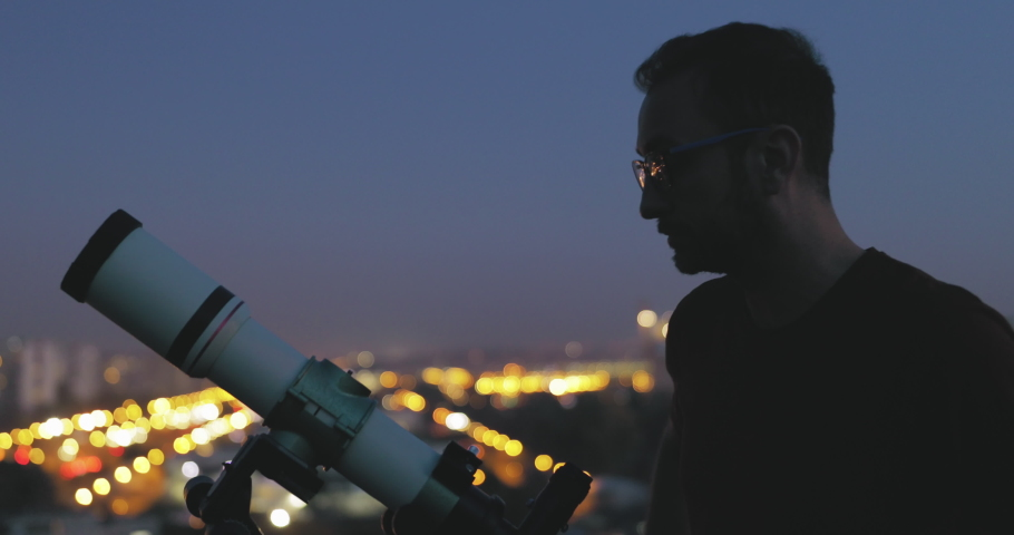 Astronomer with a telescope watching at the night sky with blurred city lights in the background. Royalty-Free Stock Footage #1056430784