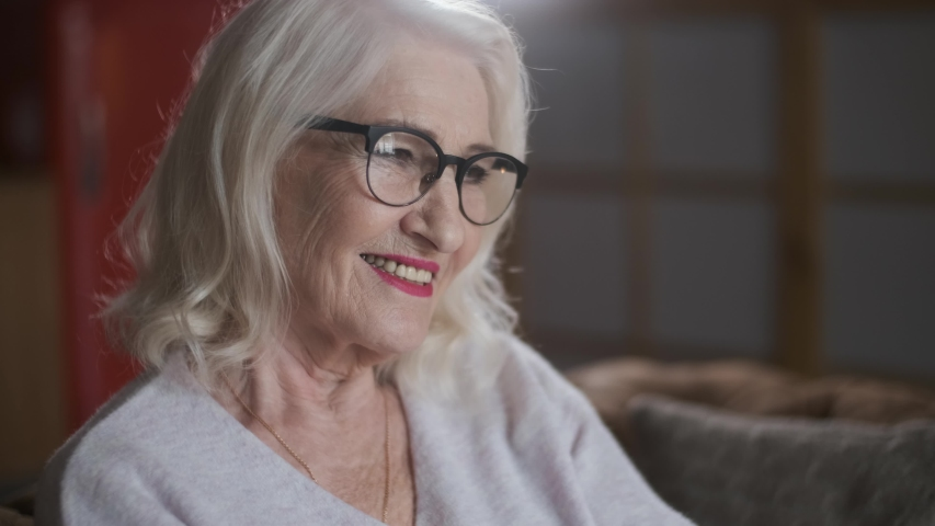 Portrait of a lovely, smiling elderly woman with glasses.