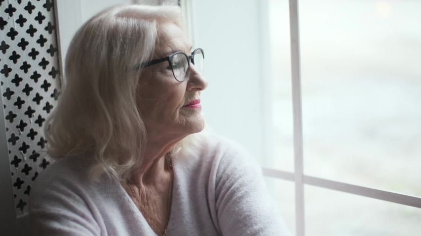 Portrait of a lovely, smiling elderly woman with glasses. Grandma looks out the window.