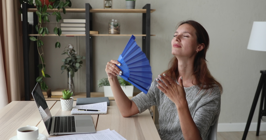 Woman employee sit at workplace desk use blue fan cooling herself in office without air conditioner. Hot summer day, thirsty unhealthy female hormonal imbalance, discomfort due unbearable heat concept