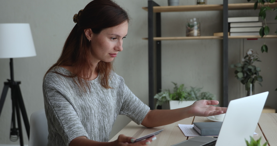 Woman sit at desk use laptop holding plastic card having problems, transaction rejected, failed due not enough money on bank account. On-line payment failure, internet scam fraud theft victim concept Royalty-Free Stock Footage #1056440240