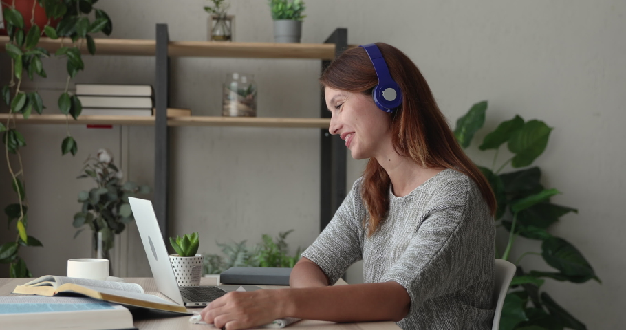 Student girl sit at desk writing notes work on text translation with classmate, prepare for college exams together by videocall use headphones and laptop. Videoconference distant communication concept Royalty-Free Stock Footage #1056440270