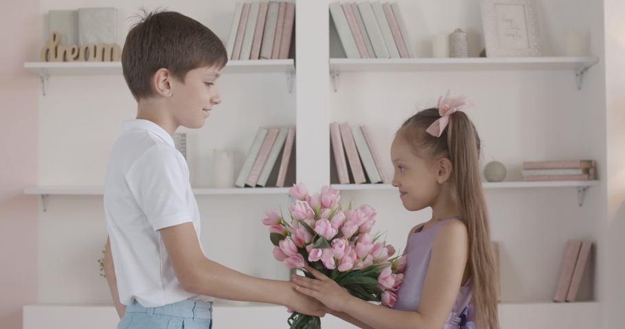 Caucasian boy giving bouquet of flowers to shy little girl. Side view portrait of cute gentleman congratulating pretty child indoors. Concept of first love, childhood.