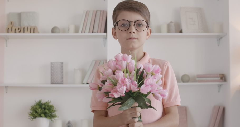 Nerd little boy stretching bouquet of flowers to camera and smiling. Portrait of smart Caucasian kid in eyeglasses holding pink tulips at the background of bookshelf. Child giving gift for holiday.