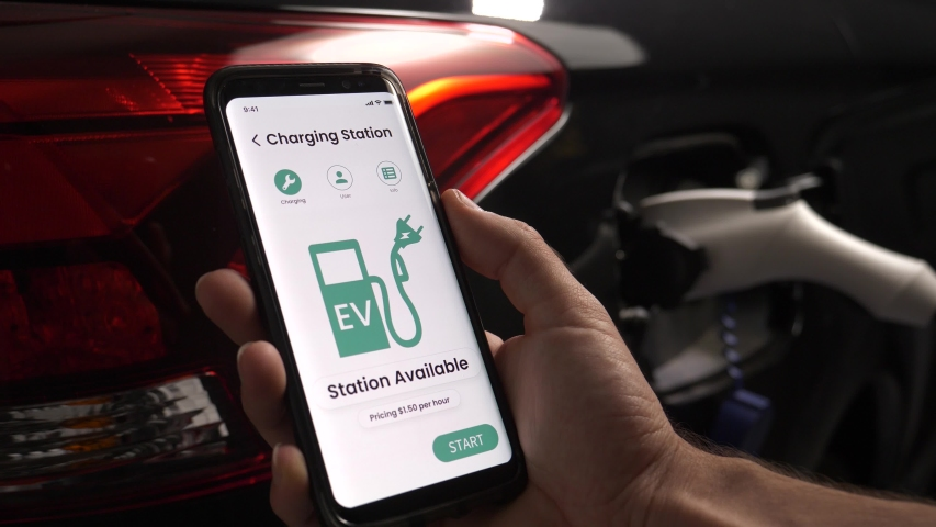 Connecting to the charging station with a mobile phone to be able to start charging the EV car. Electric vehicle in the background being plugged to the charger. Royalty-Free Stock Footage #1056441527