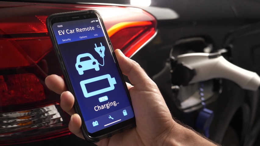 Mobile phone showing the charging status of an EV vehicle being charged in the background. Royalty-Free Stock Footage #1056441551