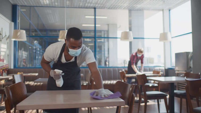 African male worker cleaning table with disinfectant in restaurant during coronavirus outbreak. Waiter in protective mask and gloves disinfecting table with spray and cloth Royalty-Free Stock Footage #1056442013