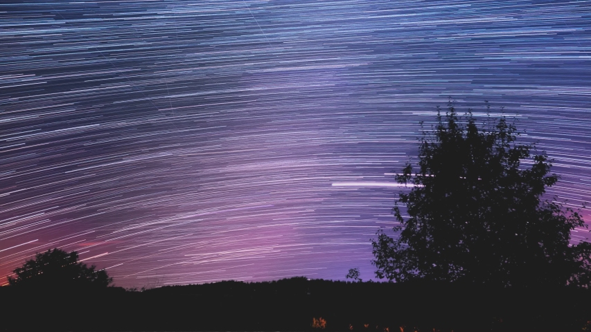 Star trail Time-lapse 4k footage of the stars behind a lone tree in the night sky. Milky Way galaxy orbiting over a mountain