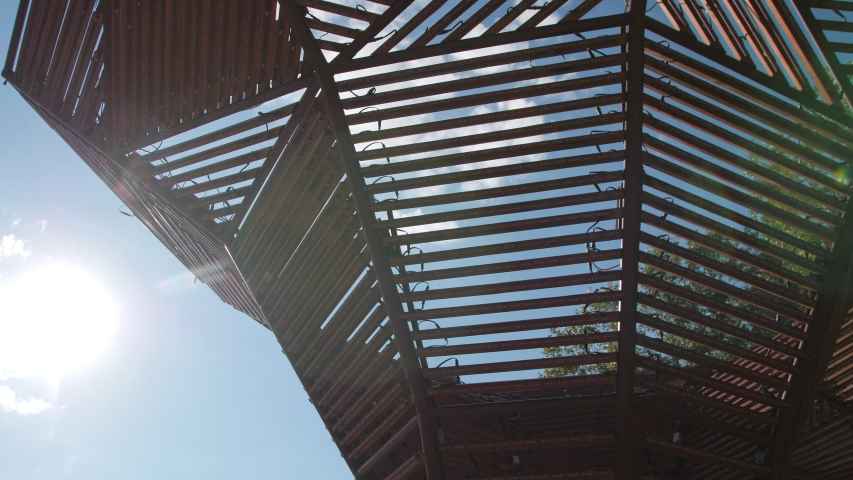 Wooden arbor roof made with thin planks against translucent blue sky with white clouds in spring park low angle shot closeup